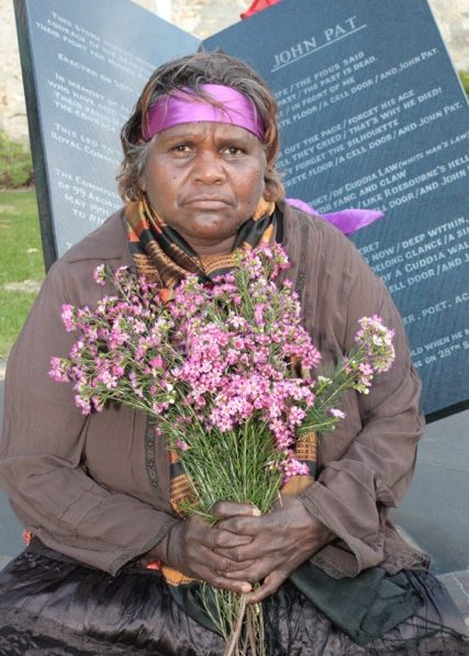 Daisy Ward sits in front of a memorial for John Pat at the Fremantle prison, holding a bunch of pink flowers. She is looking directly into the camera lens.