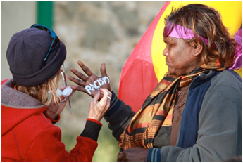 Daisy Ward stands side-on, in front of an Aboriginal flag at the Fremantle prison. Her hand is held up while a woman paints the word 'racism' on her palm.