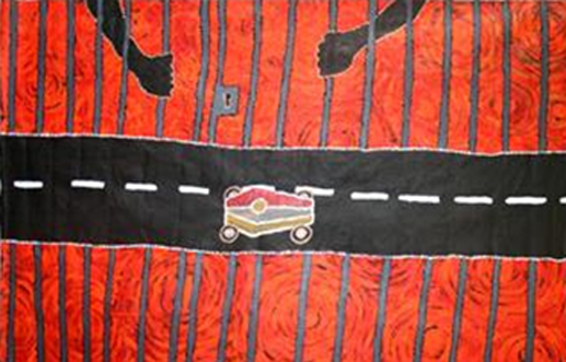 A painting depicts a red landscape. A road cuts horizontally across the landscape and a coffin marked with Aboriginal flag, on wheels traverses the road. Prison bars vertically score the land. Black hands grasp the bars.