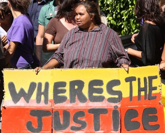 "A woman at a protest holds a large, painted cardboard placard that reads ""Wheres the Justice""."