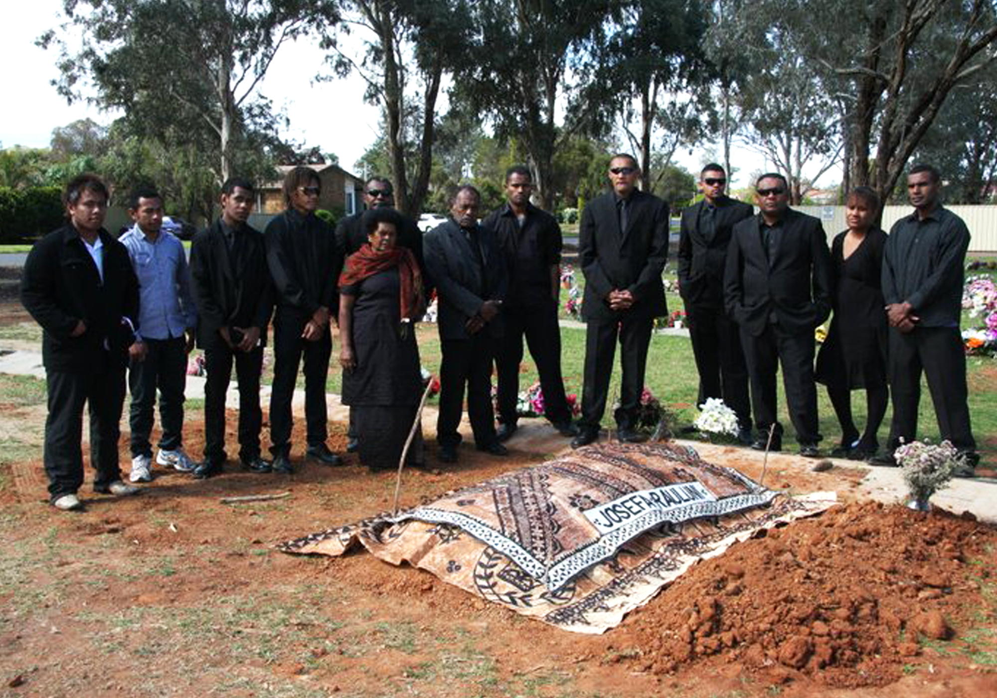 Mourners dressed in black are gathered at the site of Josefa Rauluni's grave.