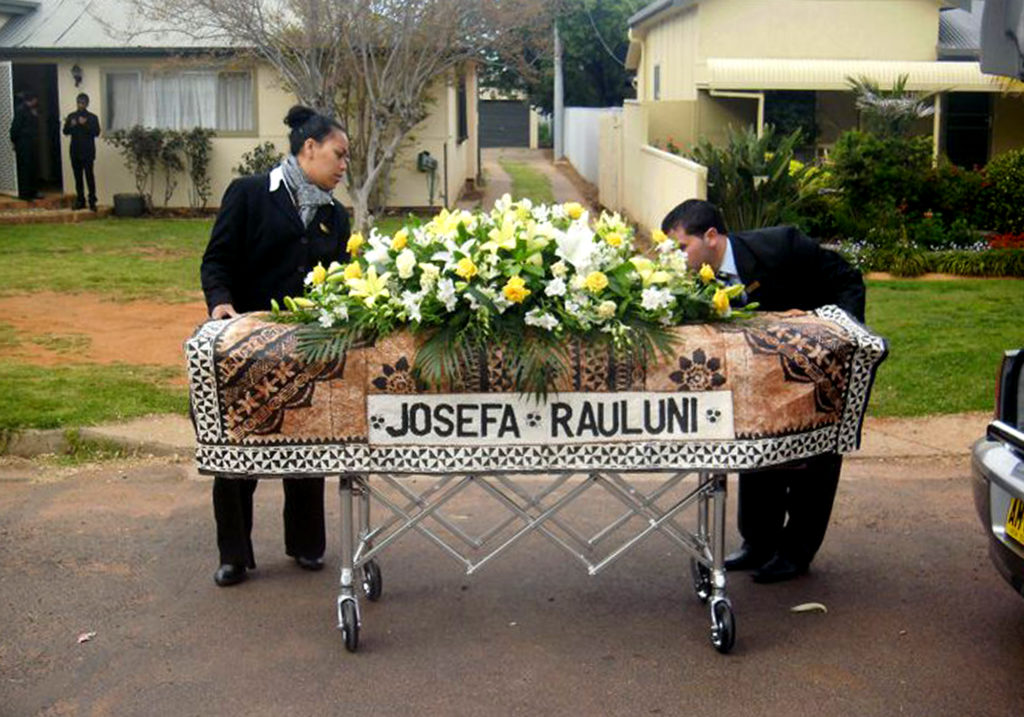 Two people stand behind a coffin shrouded with a covering bearing Josefa Rauluni's name and adorned with white and yellow flowers. They stand on a suburban street and appear to be transporting the coffin from one place to another.