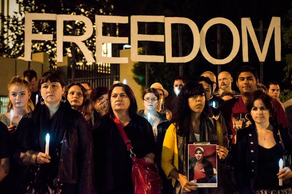 Photo taken at a vigil for Saeed Hassanloo outside the Royal Perth hospital. A crowd gathers holding candles. Letters spelling 'FREEDOM' are held up behind the crowd.