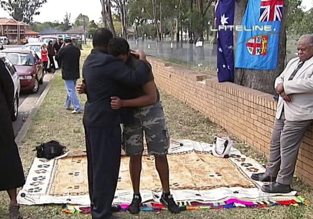 Two men embrace outside Villawood IDC between a fence and the suburban street. They and other community members are gathered to grieve Josefa Rauluni's death.