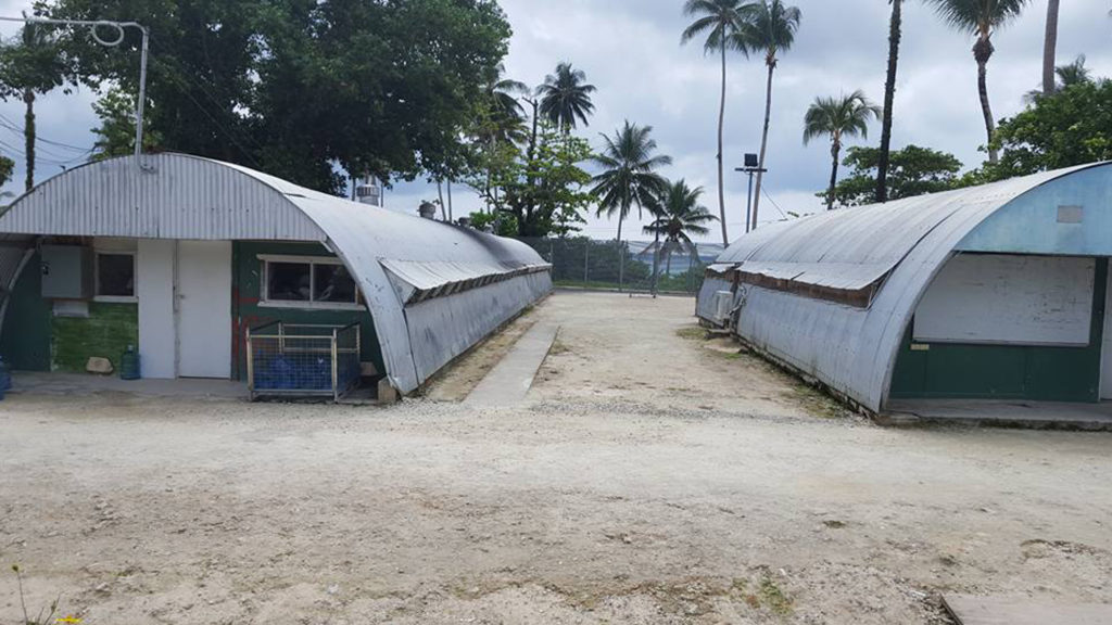 Two weather Nissen huts are pictured in the Delta Compound of the former Manus RPC at Lombrum. Fences and palm trees can be seen in the background.