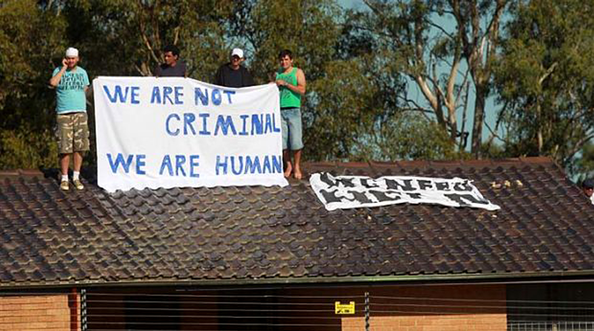 Four men stand on the roof of a building in the Villawood IDC. They raise a banner that reads, 'We are not criminal. We are human.'