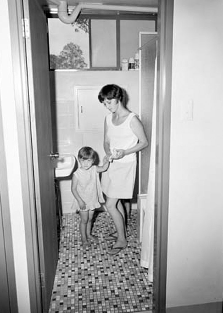 A black and white photo depicts a woman and child inside the bathroom at the Villawood Migrant Hostel.