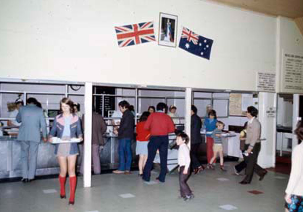 Adults and children collect a meal from the mess hall of the former Villawood Migrant Hostel. The English and Australian flags are hung on the wall above.