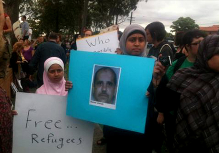 Two girls are pictured in a crowd at a protest outside outside Villawood IDC. One carries a placard with Ahmed Al-Akabi's photo on it, another carries a placard that reads 'Free...Refugees'.