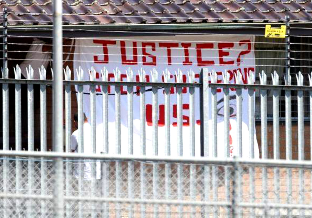 A banner painted with red writing reads 'Justice? Stop Suffering Us'. It is held up during a protest behind layers of fences at Villawood IDC.