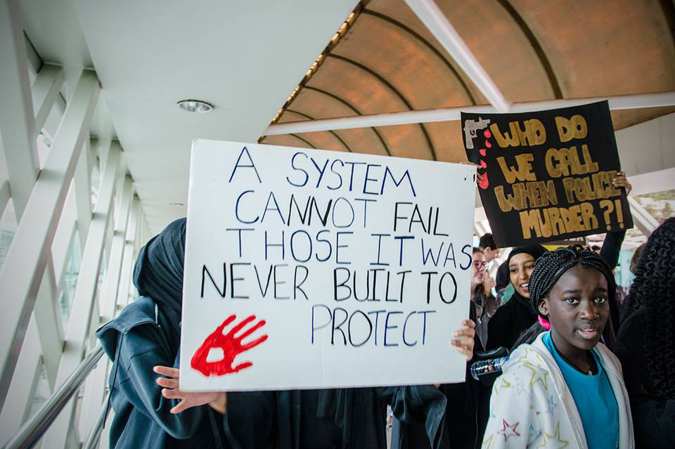 A placard carried at a Black Lives Matter protest and visible in the foreground reads 'A system cannot fail those it was never built to protect'. Another placard further back in the crowd reads, 'Who do we call when police murder?!'