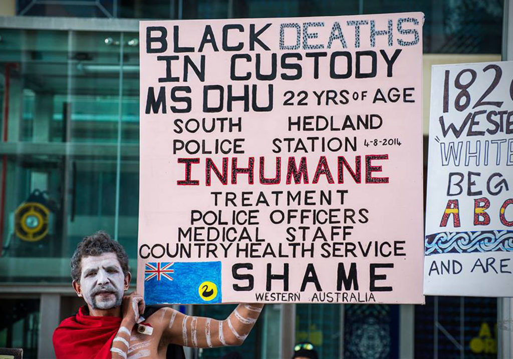A man, raises a large square placard at a protest. His face and body are painted and an Aboriginal flag is draped around his neck. The placard reads, 'Black Deaths in Custody Ms Dhu. 22 yrs of age. South Hedland Police Station 4-8-2014. Inhumane treatment police officers, medical staff, country health service. Shame Western Australia.'