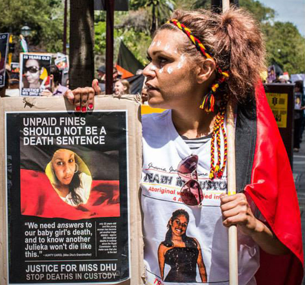 A woman pictured at a protest carrying a placard reading 'Unpaid fines should not be a death sentence' in one hand and an Aboriginal flag in another. She wears a shirt with Ms Dhu's photo on it and a plaited headband of red, yellow and black.