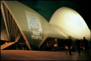 A photo of an old ship with the words 'Boat People' below, projected onto the Sydney Opera House.