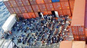 A large group of people are viewed from above, sitting on a large ship (The Tampa). Orange shipping containers frame the view.