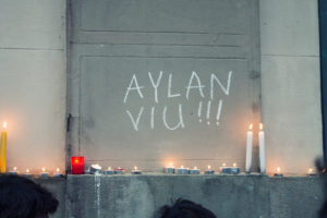 "Vigil for Alan Kurdi. background wall showing a writing on a wall of ""Alan is alive"" in Catalan"