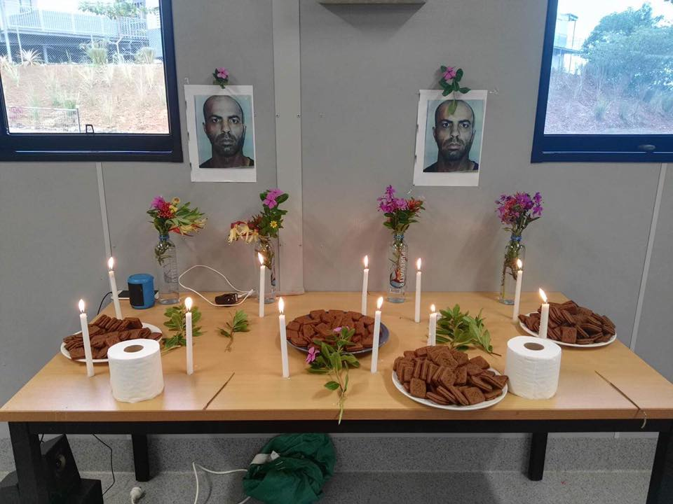 Photos of Hamid Shamshiripour are stuck on the interior walls of a building at the East Lorengau Transit Centre. A table adorned with flowers, candles and biscuits is placed in front of the wall.