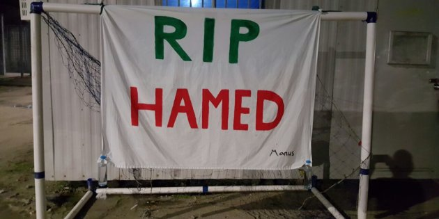 A banner that reads 'RIP HAMED' is hung from a soccer goal post inside the former Manus Island prison.