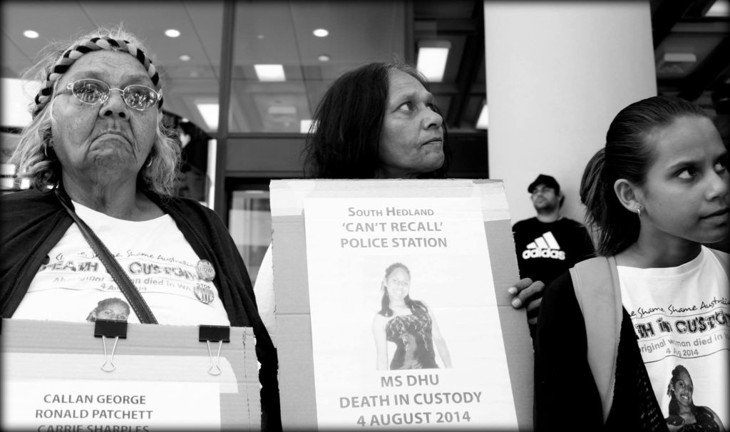 Aunty Carol, Della Roe and Yolanda stand beside one another outside the Coroner's Court. Aunty Carol and Della both hold placards - one reads 'South Hedland 'Can't Recall' Police Station. Ms Dhu Death in Custody 4 August 2014'.