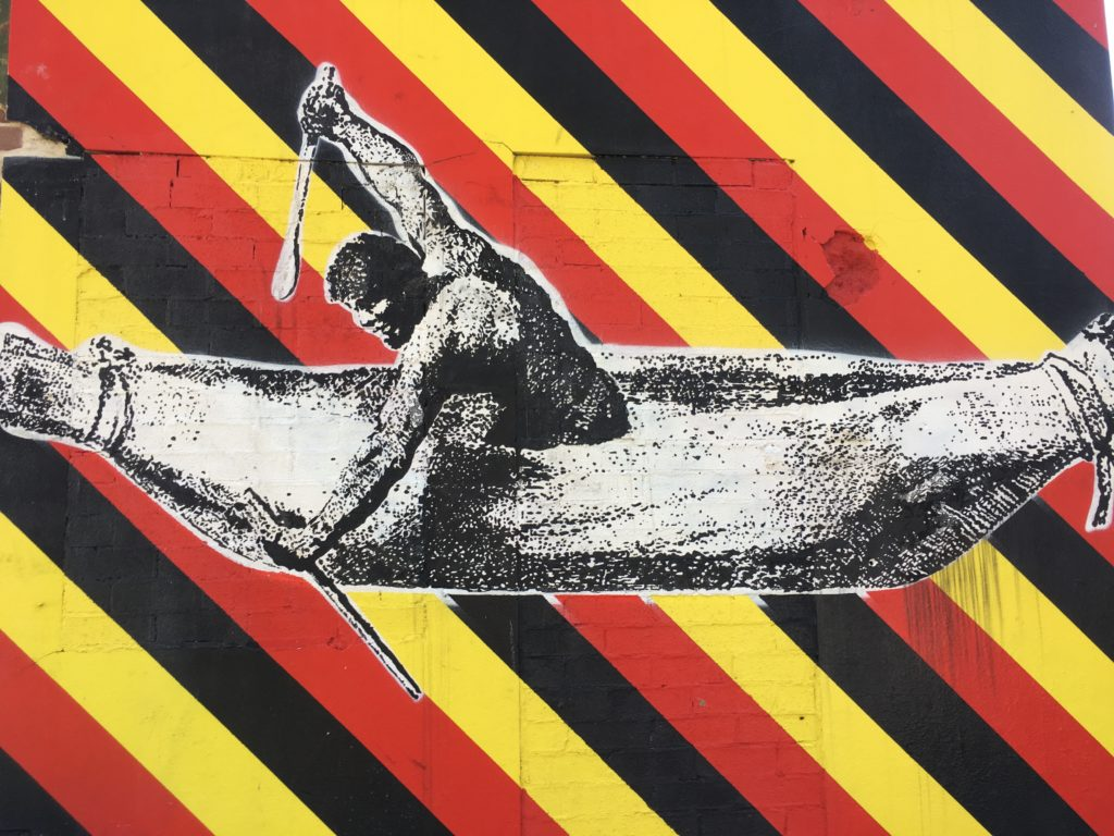 A depiction of Pemulwuy, by Samuel John Neele, where he is rowing a canoe is cut out and layered above bold red, black and yellow diagonal stripes painted on a building.