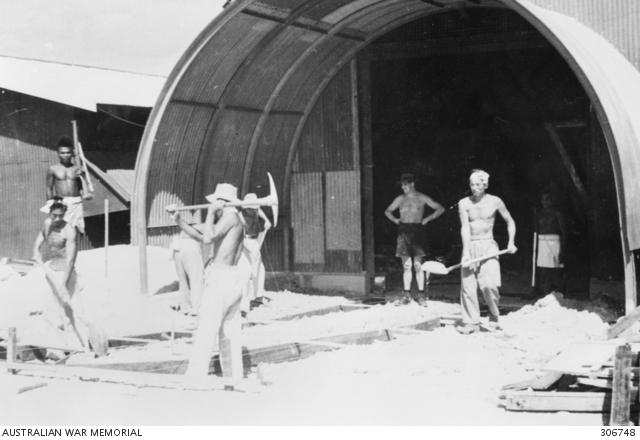 Shirtless workers are shown in front of a Nissen hut with shovels and other tools.