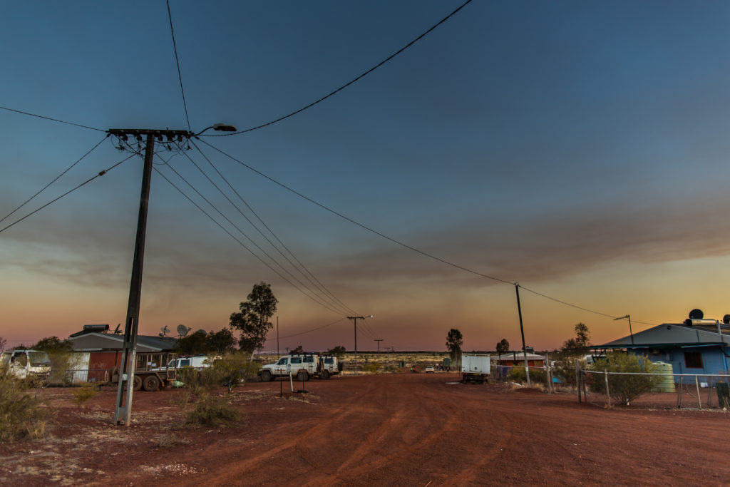 A red dusty street in the Patjarr community is pictured at dusk. A power pole and electrical lines connect to houses. Vehicles and other signs of domestic life are present.