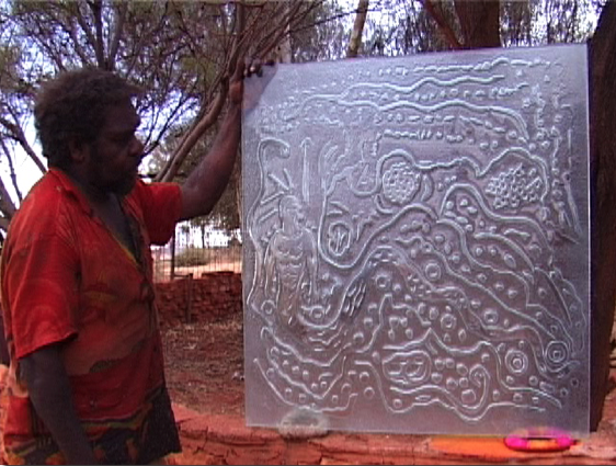Mr Ward holds up his artwork (an art glass panel) 'Wati Warnampi at Tartjarr – Rainbow Serpent Man at Tartjarr Soak'.
