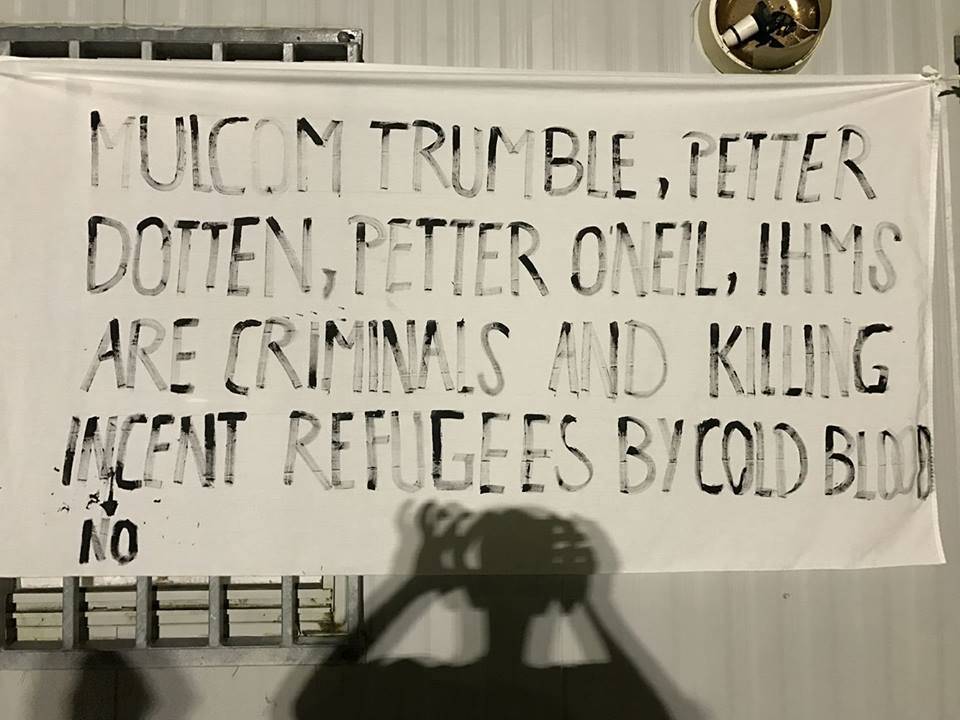 "A banner hung for a memorial service in the Manus prison reads, ""Mulcom Trumble, Petter Dotten, Petter O'Neil, IHMS are criminals and killing innocent refugees by cold blood""."