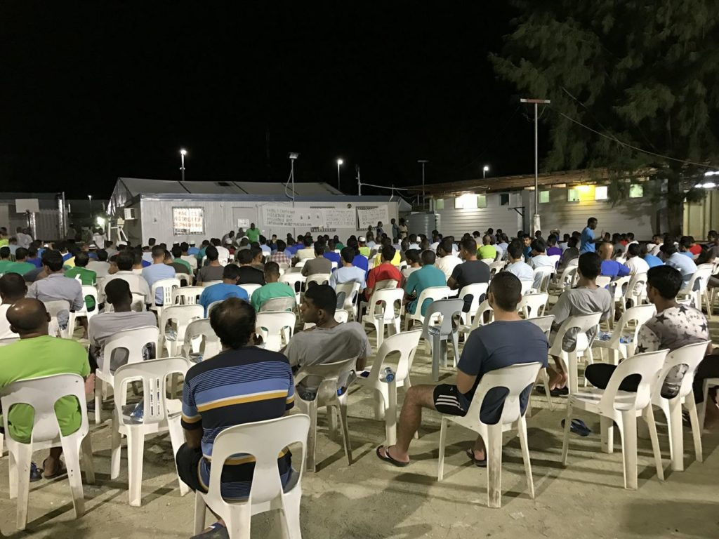 A vigil for Faysal in the Manus prison. It is night time and dozens of plastic chairs are assembled outside facing a small building that banners are attached to. Speakers address the crowd.