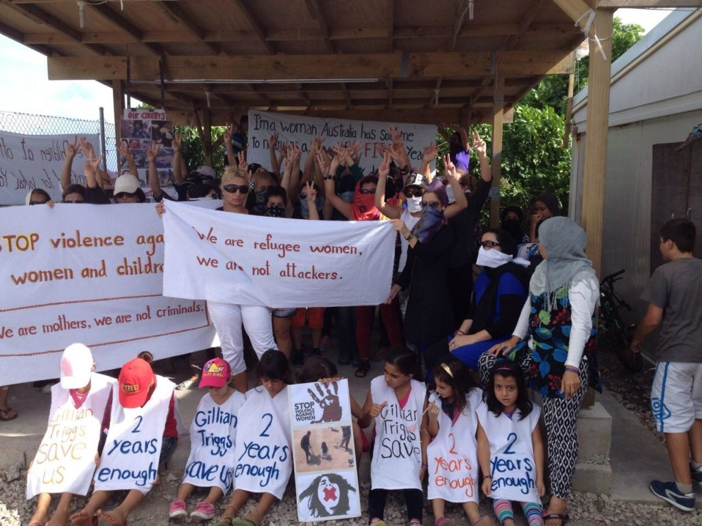 Women stand under a verandah with banners. Children sit at the front wearing aprons painted with slogans like '2 years enough' and 'Gillian Triggs save us'. The women hold banners including one that reads 'We are refugee women, we are not attackers'. Those not holding banners hold their hands in the air showing peace signs.