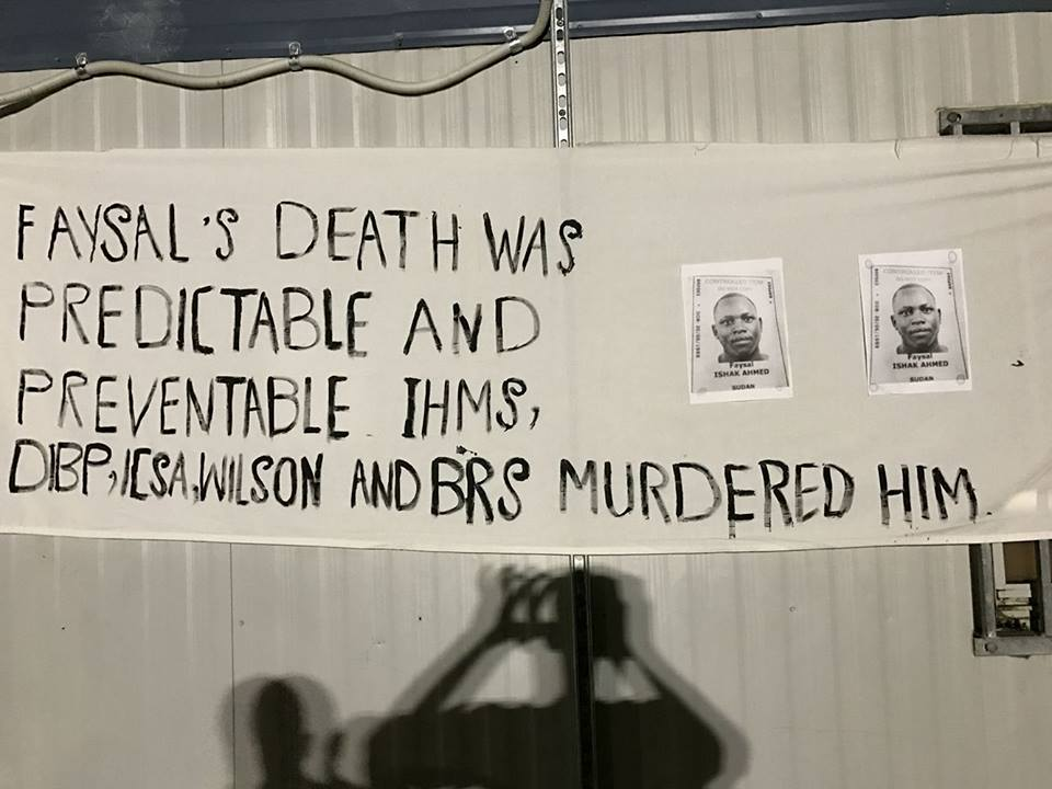 "A banner hung for a memorial service in the Manus prison reads ""Faysal's death was predictable and preventable IHMS, DIBP, ICSA, Wilson and BRS murdered him."". Two black and white photos of Faysal's detention centre ID card are attached to the banner."