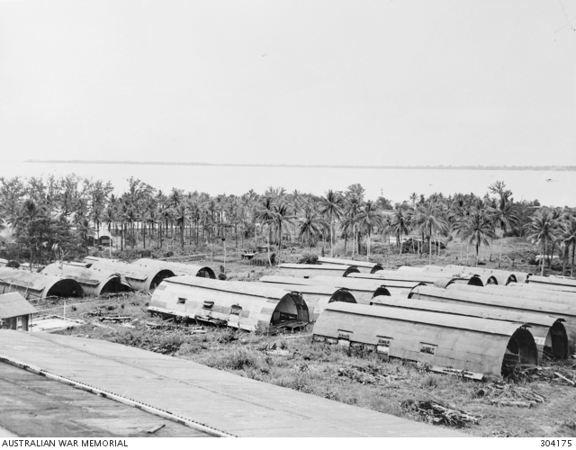 A black and white photo shows a slightly elevated view of rows of military Nissen huts in the foreground. The background shows palm trees.