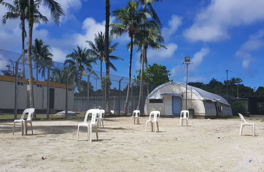 A Nissen hut is pictured in the former Manus RPC. White plastic chairs are scattered on the sand in the foreground. Fences and palm trees are in the background.