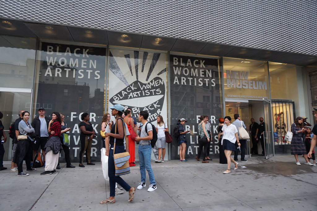 People line up outside the New Museum. Graphics on the windows advertise the exhibition of work of 'Black women artists'.