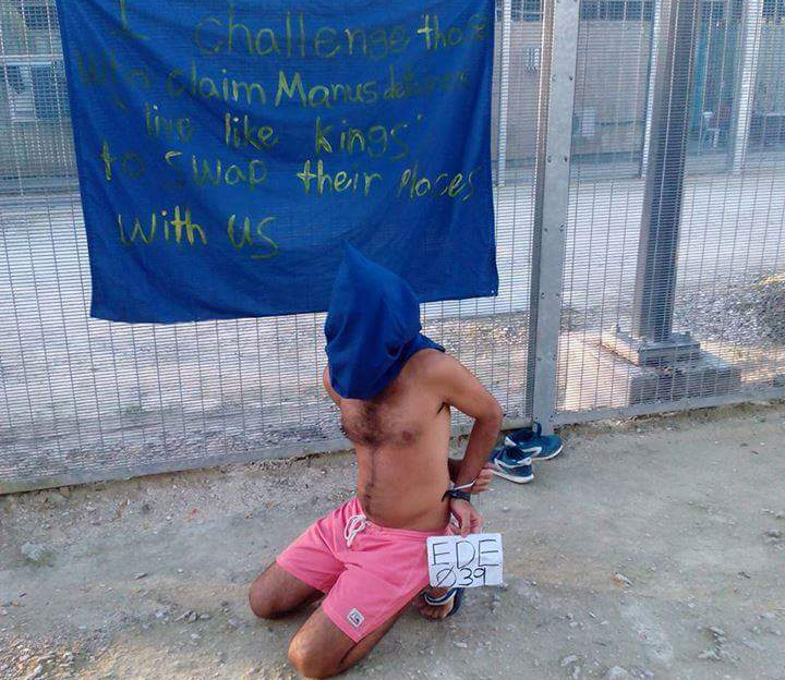 "A shirtless man protests, kneeling on the ground, with a cloth bag or hood pulled over his head and hands tied behind his back. He holds a piece of paper declaring his boat ID EDE039. A banner is hung on a fence directly behind him which reads, ""I challenge those who claim Manus detainees 'live like kings' to swap their places with us""."