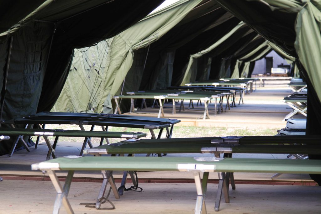 A view from inside a row of green army tents on Nauru, showing rows of stretcher beds.