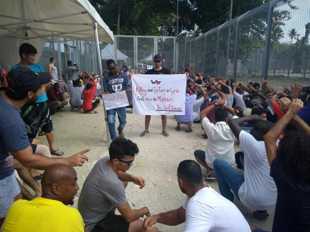 Protest in Manus Island camp. Man in centre carries banner that reads 'War killing and torture in Syria and now in Manus. The last Syrian.'