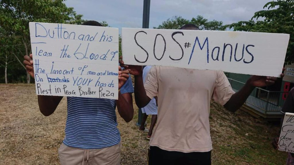 Two men detained by the Australian government on PNG stand beside one another, holding signs in front of their faces. One says 'Dutton and his Team the blood of the innocent of men and women on your hands. Rest in Peace Brother Reza' and the other reads 'SOS#Manus'. They stand outside the East Lorengau transit accommodation. Dried grass and trees are visible in the background.