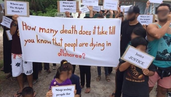 "Adults and children protest on Nauru. A banner is held up that reads, ""How many death does it take till you know that peopl are dying in offshores?"". Placards calling for justice and ""helping hands"" are also held."