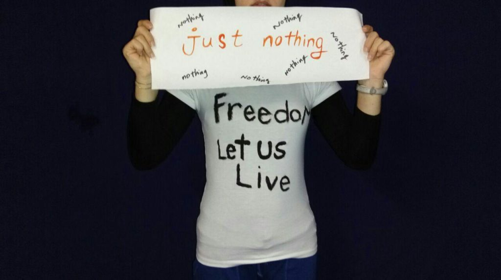 A woman holds a piece of paper to the camera which reads 'just nothing' with the words 'nothing' repeated around the page. She wears a t-shirt with the words 'Freedom Let Us Live' painted on them. The frame shows only her shirt, arms and sign.