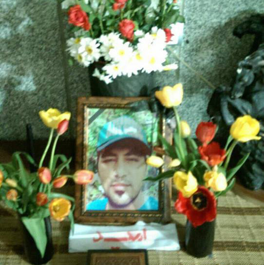A framed photo of Omid is in the centre, with a large bouquet of flowers behind and two smaller flower arrangements either side.