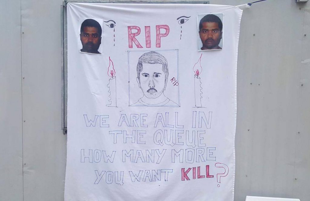 "A banner hung at a memorial service in the Manus Prison. A portrait of Rajeev Rajendran is drawn in the centre in between two candles. Two photos of Rajeev are attached to the banner. It reads ""RIP We are all in the queue how many more you want kill?"""