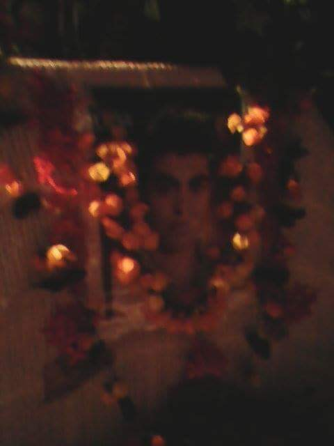 A dark and slightly blurry photo of Hamid Khazari adorned with decorations light reflects off of.