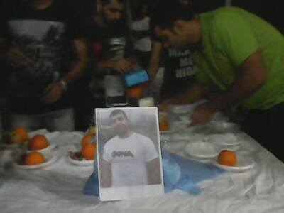 Vigil for Hamid Khazaei at the Manus Island Detention Centre. Men gather around a table, a photo of Hamid is placed in the centre and plates bearing fruit are being arranged.