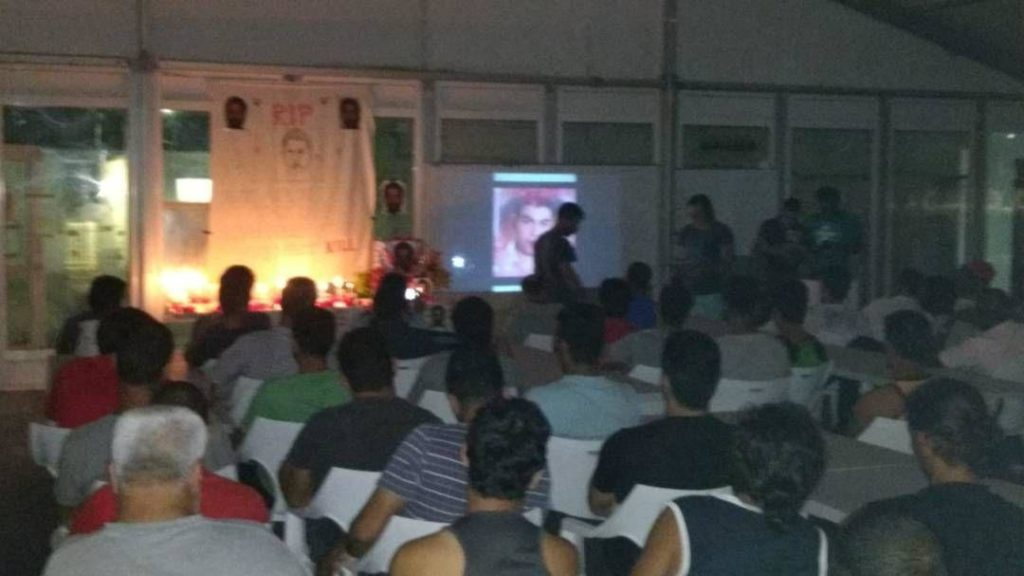 At a memorial service for Rajeev Rajendran in the Manus Prison, men face toward the front where images are being projected onto a wall. Hamid Khazaei's photo is shown.