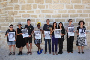 Nine people stand in a row in front of a limestone wall that forms part of the Fremantle Roundhouse. They hold placards naming the deaths of seven people as a result of Australia's border policies.