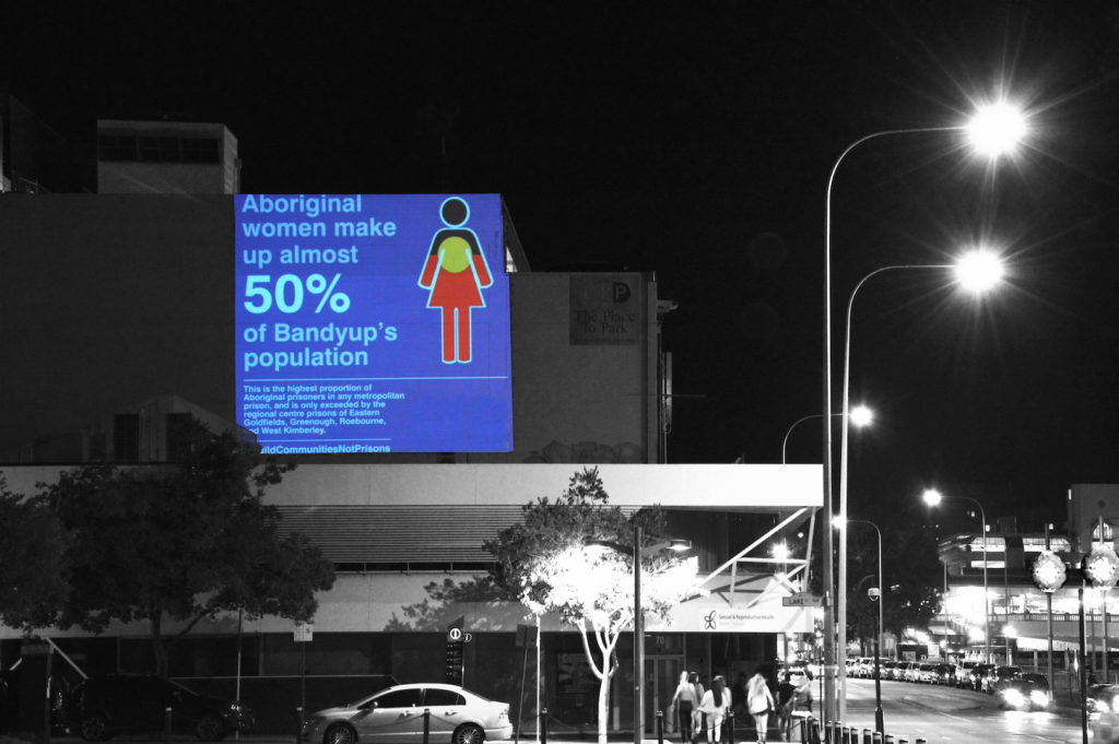 Projection at night onto a building in Perth. The projected square is an infographic that reads 'Aboriginal women make up almost 50% of Bandyup's population' and beside the text is an icon of a woman bearing the Aboriginal flag. In the foreground, street lamps, cars and pedestrians are visible.