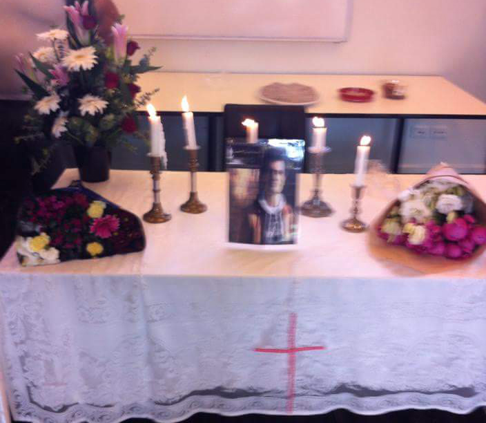 A table covered in a lace table cloth is set up in the Melbourne Immigration Transit Accommodation camp. A photo of Fazel Chegeni Nejad is positioned in the centre of the table. Five candles are placed around it with bouquets of flowers on either side. A Christian cross in marked on the table cloth. The room itself looks like it could be a classroom with part of a whiteboard visible in the background.
