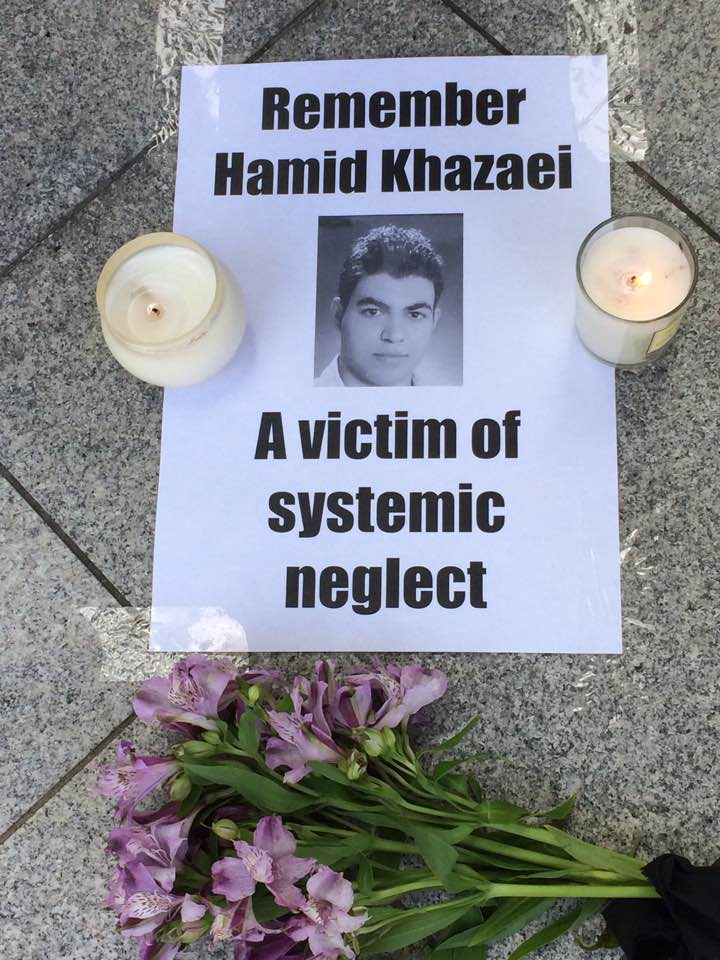 A poster placed on the pavement with two candles places either side and a bouquet of flowers below it. The piece of paper has a black and white photo of Hamid in the centre and reads 'Remember Hamid Khazaei. A victim of systemic neglect'
