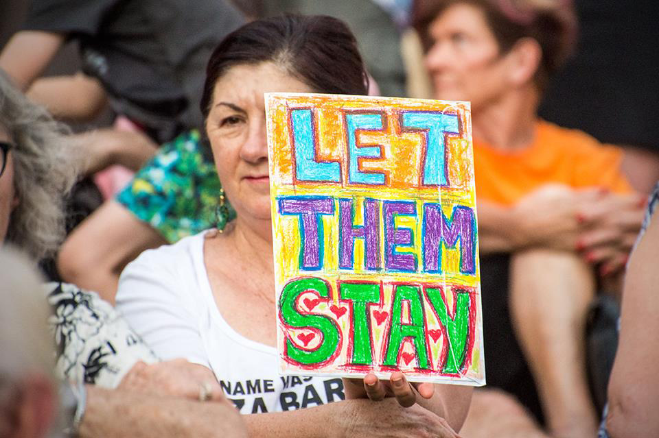 Woman holds 'Let Them Stay' poster at protest.